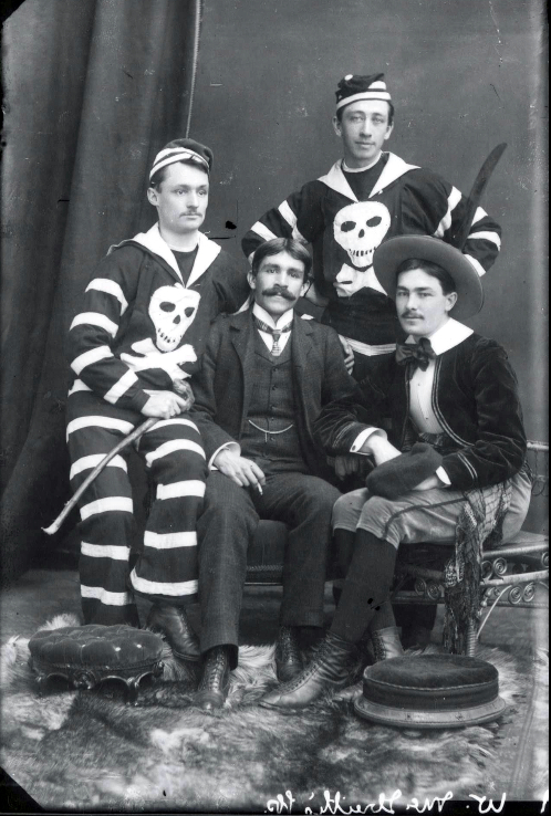 Portrait of four men from 'W. McIlreith's Group' in costume at Notman Studios in Halifax, 1885